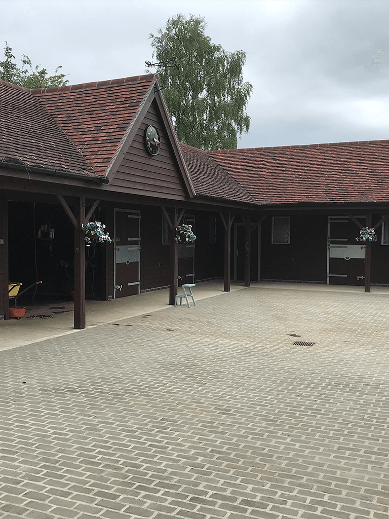 equestrian stables forming a courtyard with a wall mounted clock