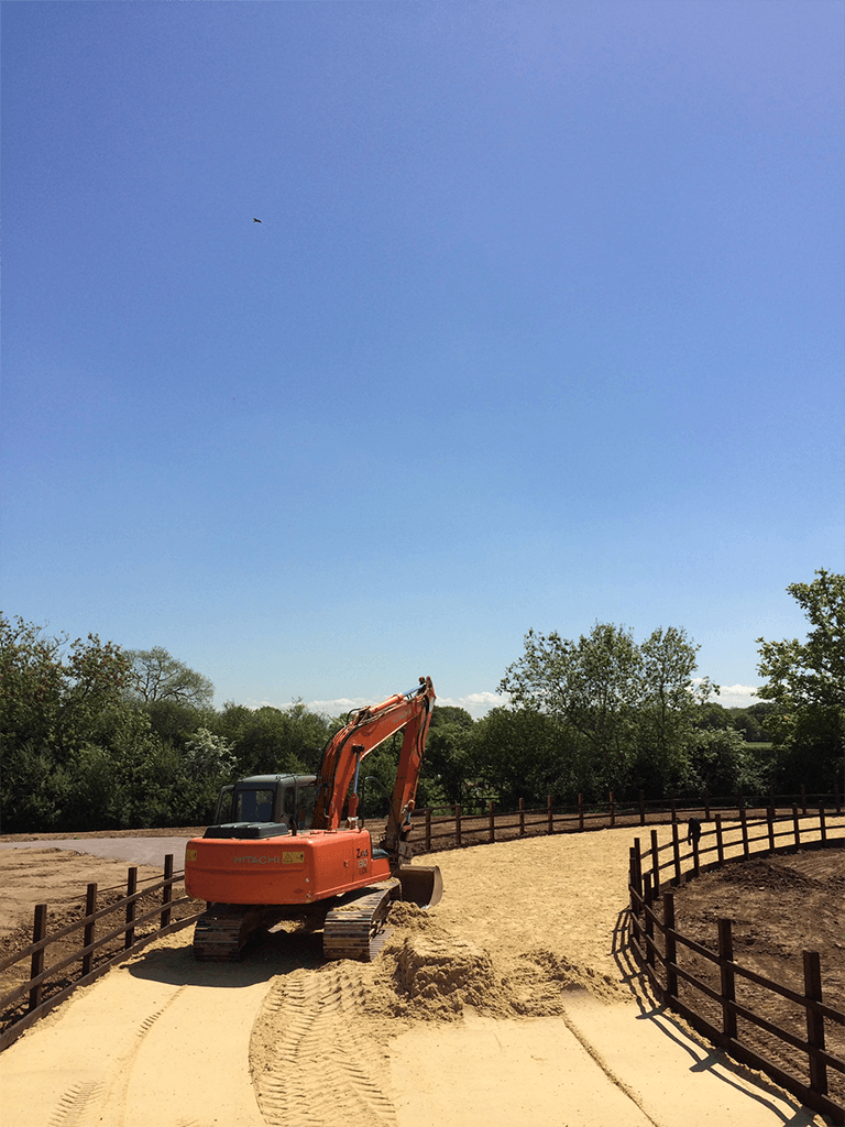 digger excavating and smoothing sand into a galloping path