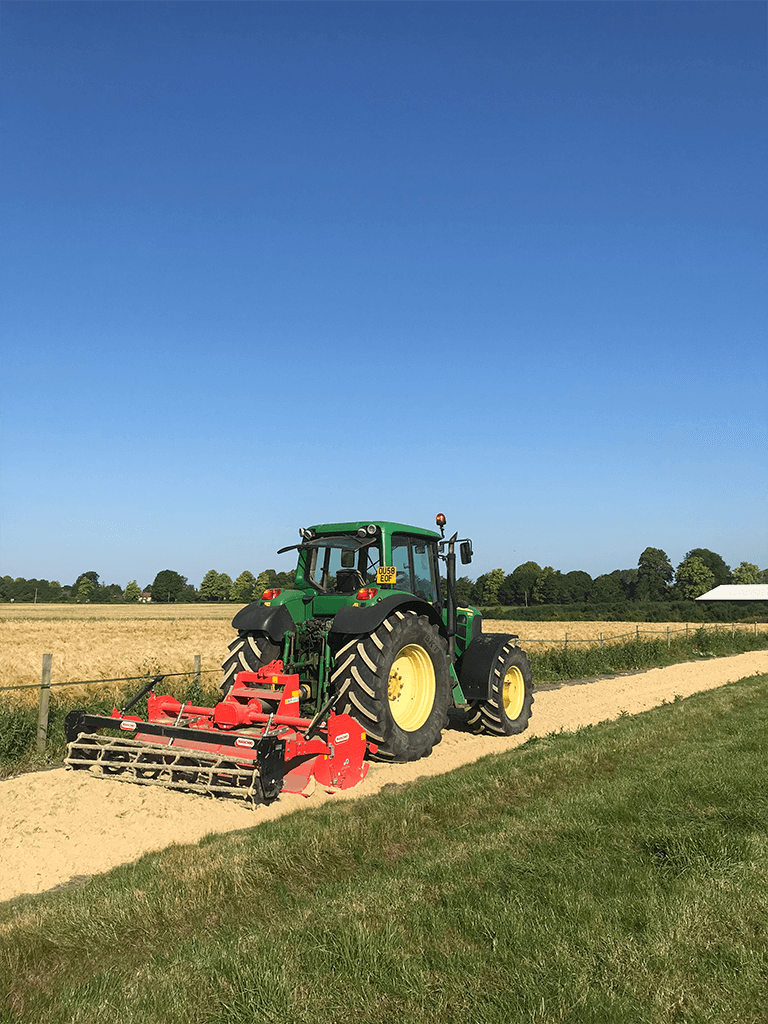 green tractor combing and smoothing out a sand gallop path